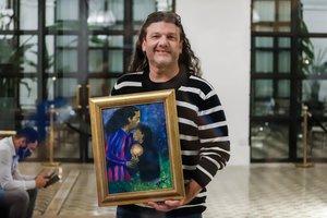 Un fan del exfutbolista posa sosteniendo un cuadro con la imagen del ídolo brasileño.