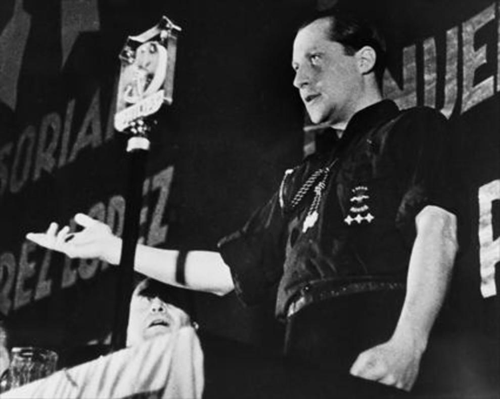 José Antonio Primo de Rivera, llevando la clásica camisa azul de Falange Española, con el yugo y las flechas bordados en el pecho, en un mítin del partido.
