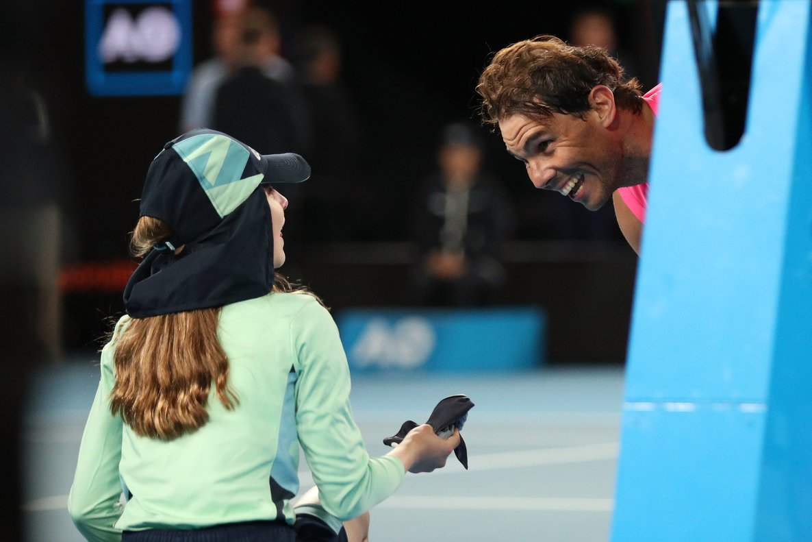 Tennis - Australian Open - Second Round - Melbourne Park, Melbourne, Australia - January 23, 2020. Spain's Rafael Nadal passes a ball girl his head band after winning the match against Argentina's Federico Delbonis. REUTERS/Hannah McKay