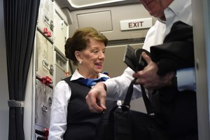 American Airlines longest serving flight attendant, Bette Nash (R), 81 years old, greets passengers disembarking from her daily return flight to Boston at Ronald Reagan Washington Airport in Arlington, Virginia on December 19, 2017.