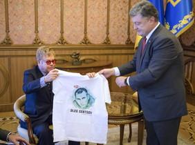 El presidente ucraniano, Petro Poroshenko, entrega una camiseta con la imagen de un cineasta encarcelado en Rusia al cantante Elton John.