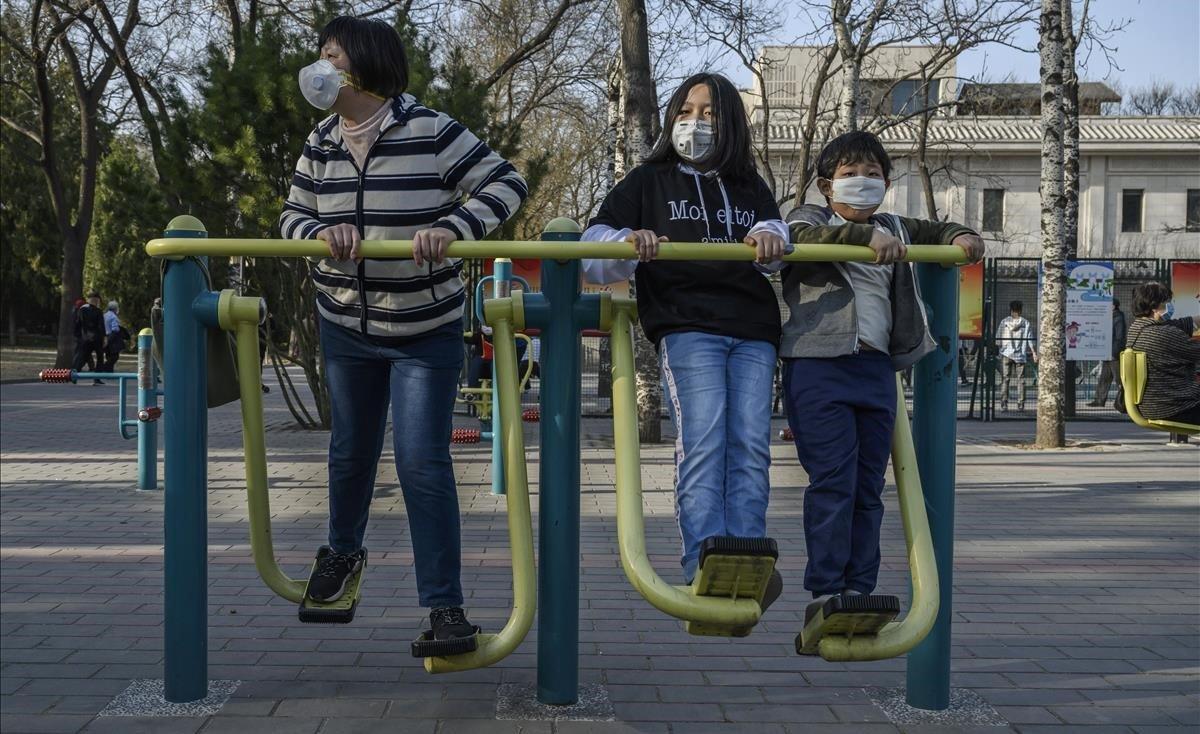 Una familia china se protege con máscaras mientras hace ejercicio en un parque de Pekín, este domingo.
