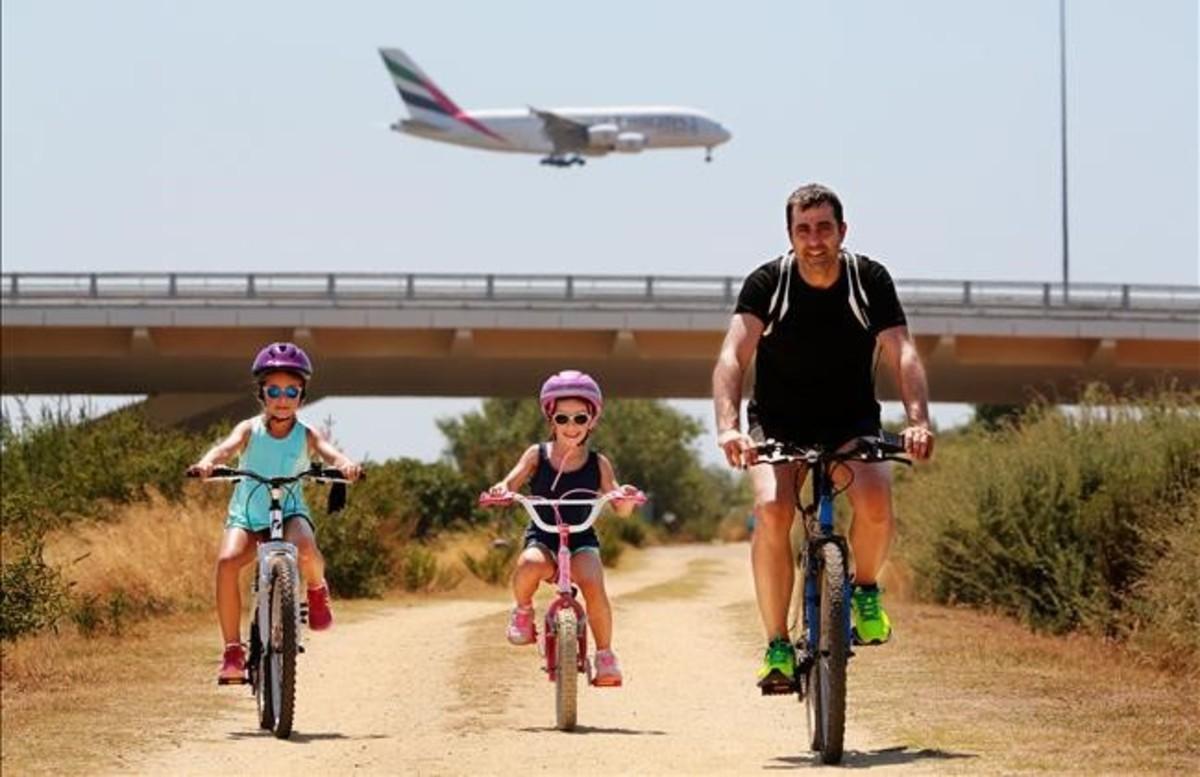 Una familia disfruta de la riqueza natural que envuelve la ruta ciclista por el delta del Llobregat.