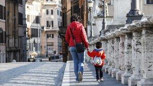 Una mujer y un niño cruzan el Puente Sant'Angelo, en Roma.