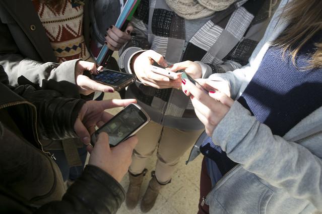 Unos jóvenes consultan sus móviles.
