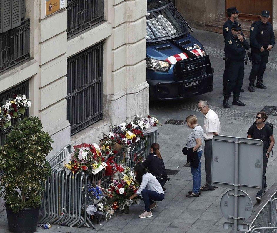 Varias personas depositan flores en la entrada de la Jefatura de la Policía Nacional en la Via Laietana.