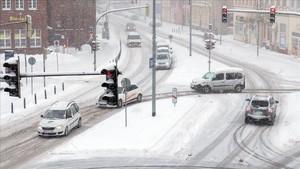 Varios coches avanzan por la carretera bajo una tormenta de nieve en Stalsund, Alemania.