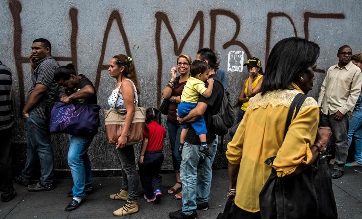 Venezolanos hacen cola frente a una pintada con la palabra hambre, en Caracas.