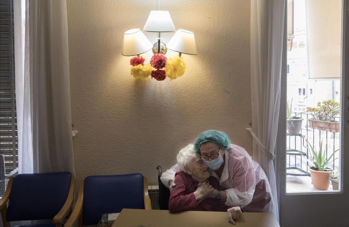 Pilar Llarc, directora de la residencia geriátrica La Pau, consuela a su madre, Pili, de 106 años y residente en el centro.