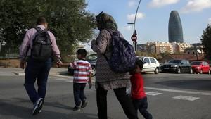 Una familia acompaña a sus hijos al colegio en el Poblenou, en Barcelona.