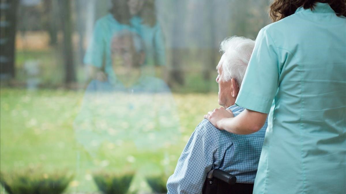 Una cuidadora con un enfermo de alzhéimer.