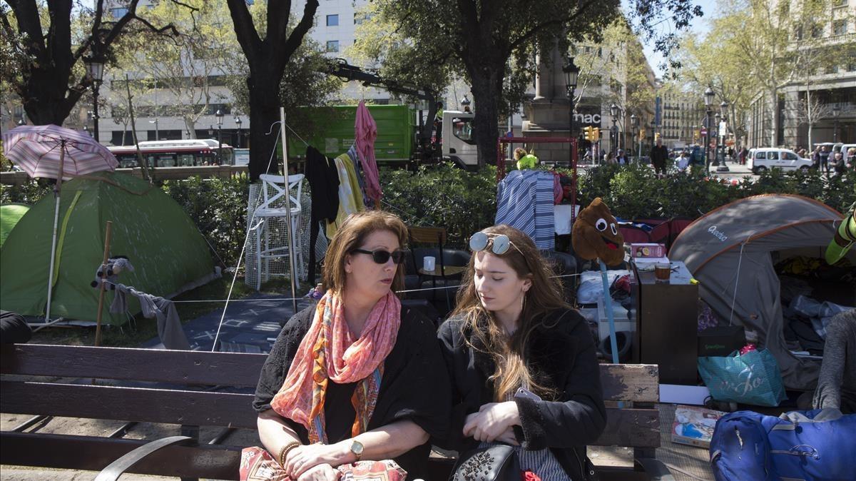 Dos turistas descansan en la plaza de Catalunya, donde unas 60 personas sin hogar acampan desde hace un mes y medio.