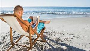 Un hombre lee en una playa.