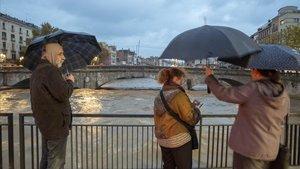 Vecinos de Girona observan la crecida del río Onyar a su paso por el Pont de Pedra de la ciudad.