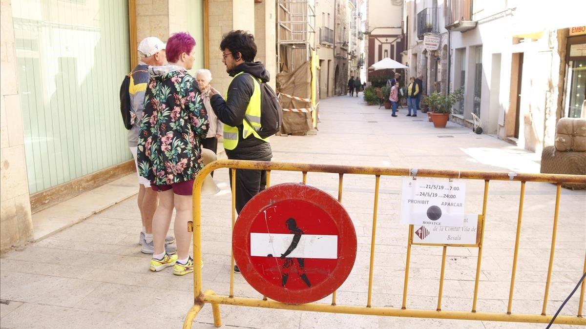 Un vigilante impide el paso a dos turistas al centro histórico de Besalú.
