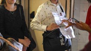Mossos de paisano examinan los documentos de unos carteristas sorprendidos en el metro.