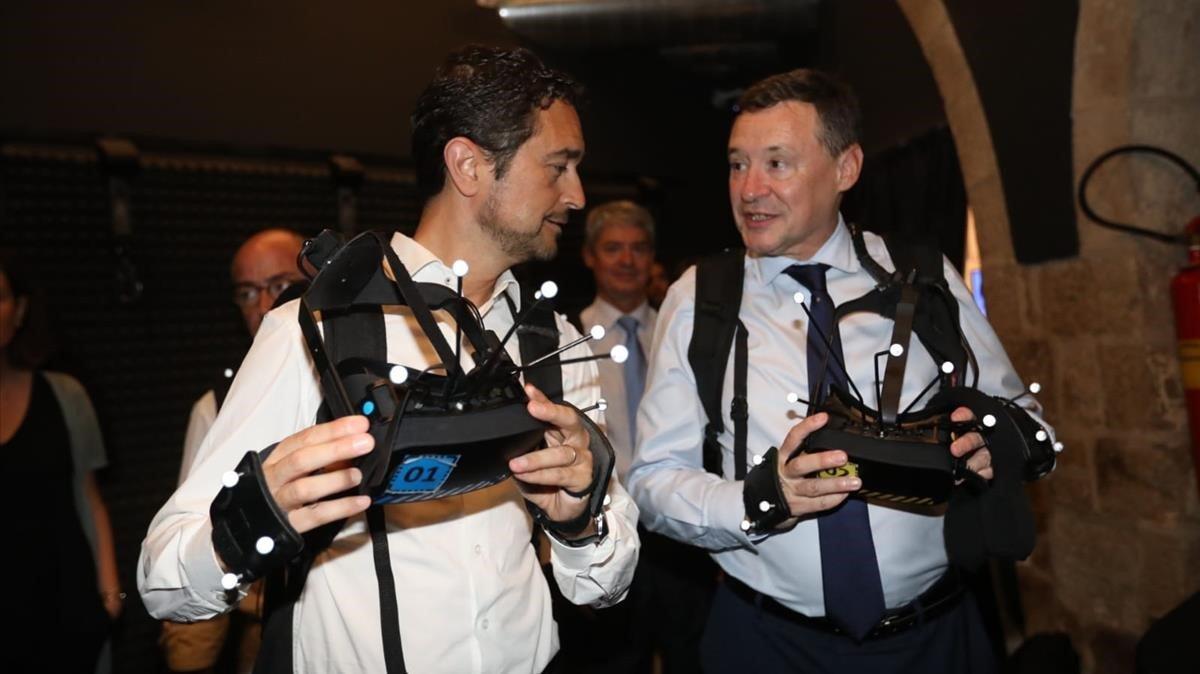 El conseller de Territori i Sostenibilitat, Damià Calvet, y el presidente del Consejo de Administración de Agbar, Angel Simón, en la exposición de realidad virtual The Zone of Hope.