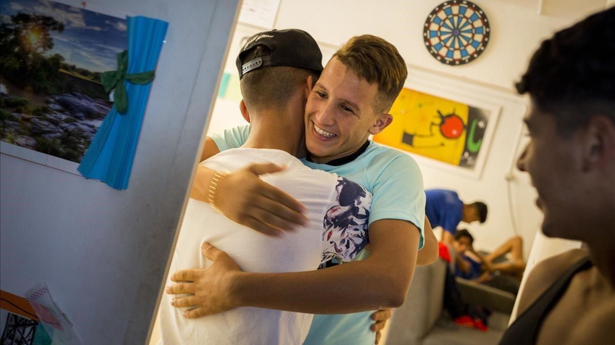 Los compañeros abrazan a Mohamed después de saber que le han asignado una plaza en un centro residencial.