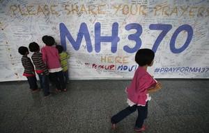 Un grupo de niños escribiendo mensajes esperanzadores para los familiares de las personas que desaparecieron en el vuelo MH370, de la compañía Malasya Airlines, en mayo del 2014.