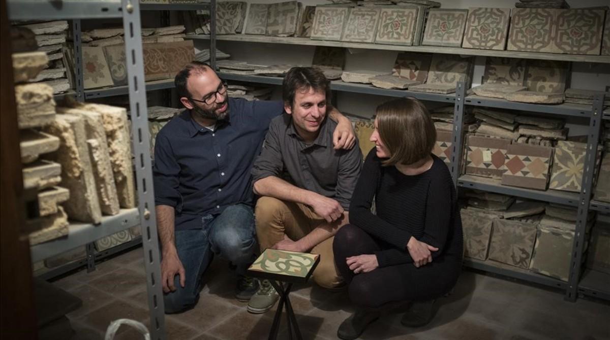 Pablo, Alberto y María, rodeados de baldosas en proceso de resurrección. Es el almacén de su marca Fragmens Bcn. Hace ocho años que las rescatan, las reciclan y las venden enmarcadaso en forma de mesa.