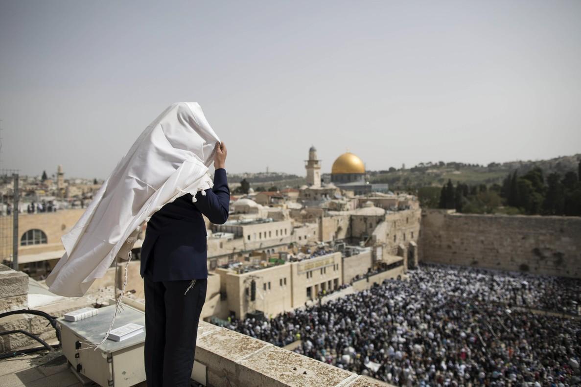 Un judío ultraortodoxo se cubre la cabeza durante la bendición sacerdotal con motivo de la celebración de la Pascua judía junto al Muro de las Lamentaciones en Jerusalén.