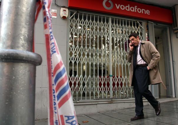 Un ciudadano habla por teléfono este miércoles al mediodía delante del escaparate destrozado de la tienda de telefonía móvil de la Rambla d'Anselm Clavé de Cornellà.