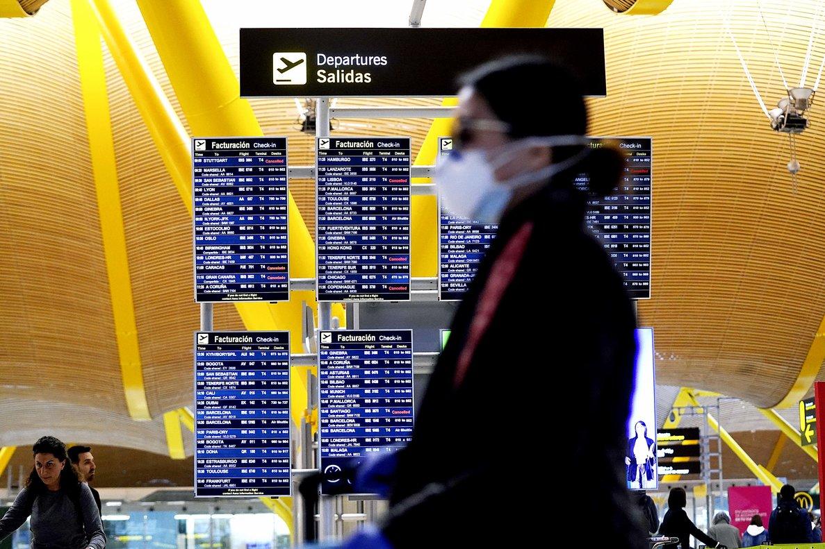 Una persona con mascarilla por el coronavirus, en el aeropuerto de Madrid.