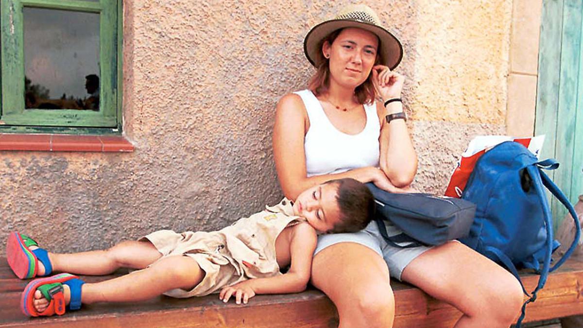 Un niño descansa en el regazo de su madre.