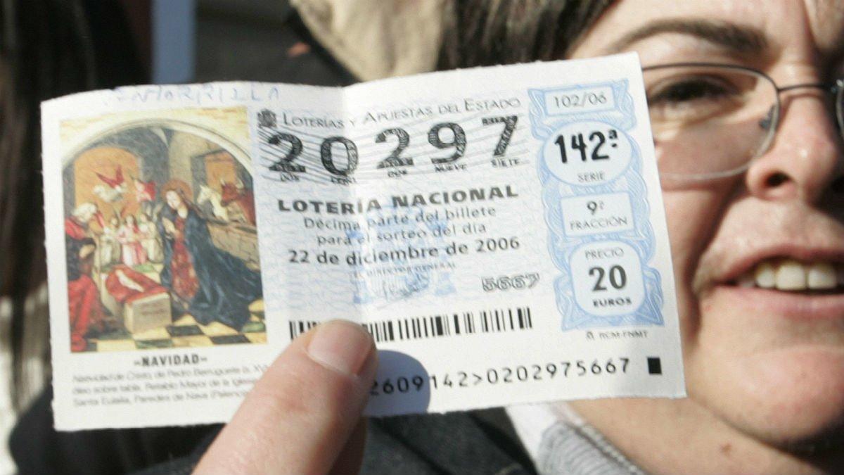 Una mujer sostiene un décimo agraciado con uno de los premios en la Lotería de Navidad.