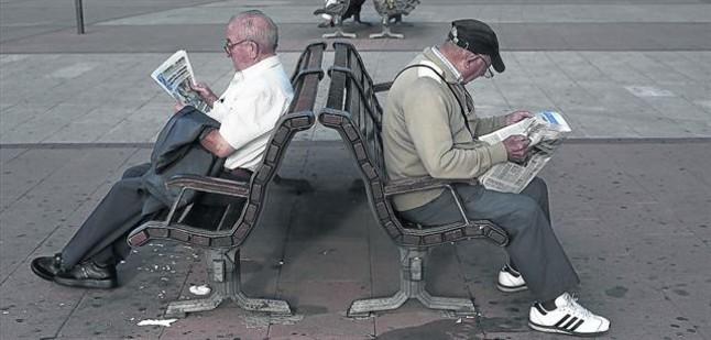 Dos jubilados leen la prensa en un parque.