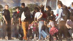Policías estadounidenses custodian a un grupo de inmigrantes que han sido detenidos por entrar ilegalmente en EEUU.