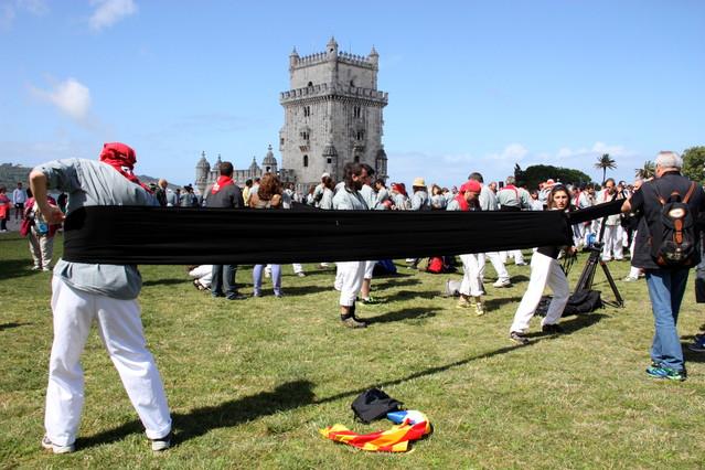 Els Castellers de Sants enfaixant-se per a un 3 de 9 davant de la Torre de Belém de Lisboa.