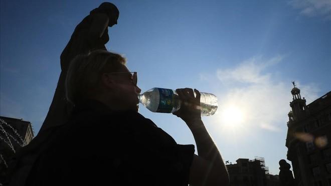 Un turista se refresca en Barcelona durante la ola de calor.