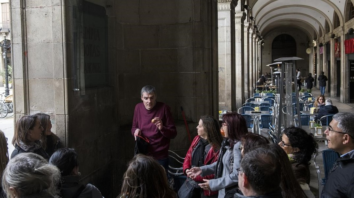 El mago Albert Trullols hace un truco en la plaza Reial durante la ruta.
