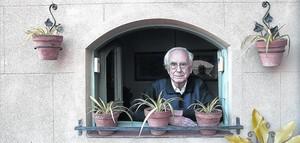 Josep Maria Espinàs, asomado a la terraza de su casa.