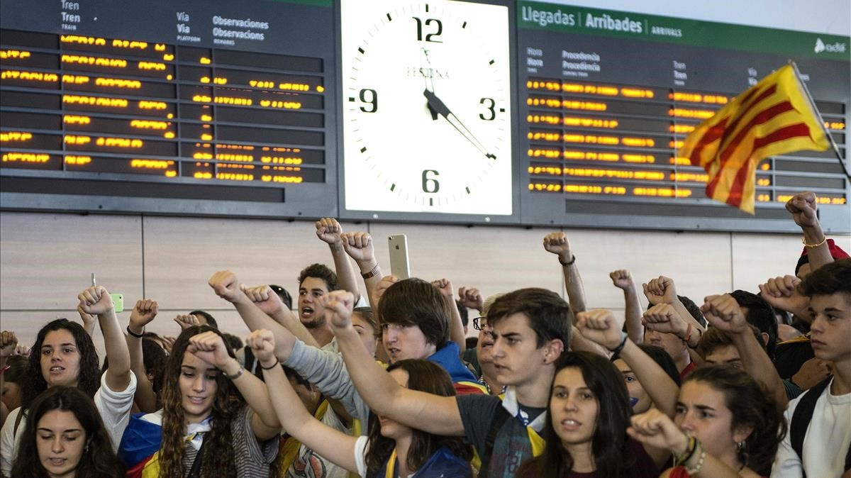 Jóvenes se manifiestan en la estación del AVE de Girona.
