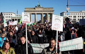 Manifestantes contra el TTIP protestan junto a la Puerta de Brandeburgo, ayer, en Berlín.