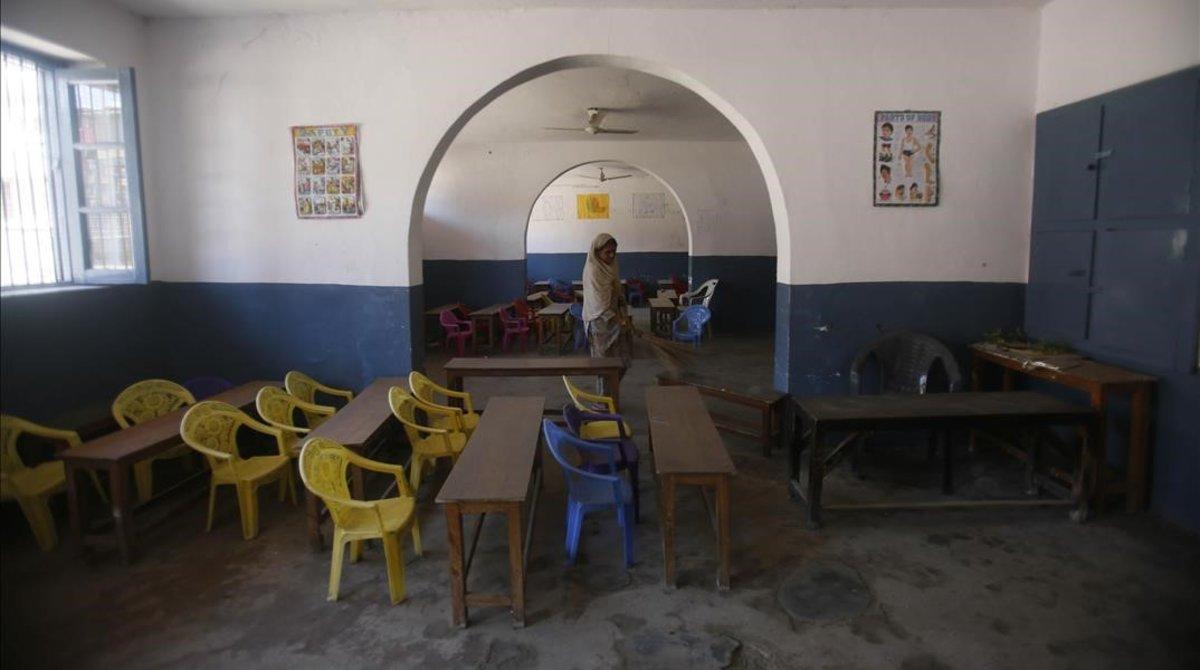 Un miembro del personal escolar limpia una aula desiertadeuna escuela de Cachemira controlada por los indios, Srinagar, 19 de agosto de 2019