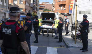 Miembros de la funeraria judicial retiran el cadáver del agresor de la comisaría de los Mossos en Cornellà.