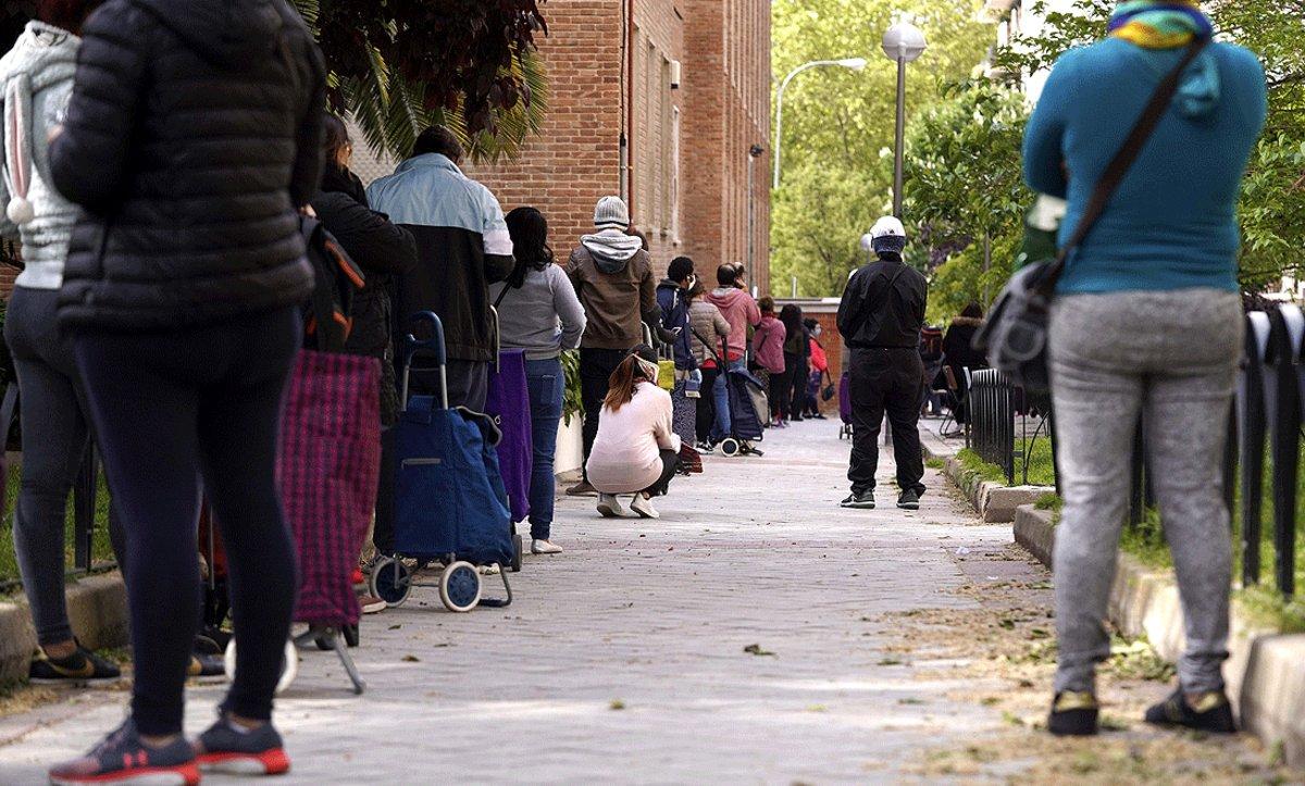 Personasesperan en la colapara recoger los alimentos que reparte la Fundación Madrina de Madrid, el pasado 28 de abril.