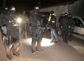 Agentes de policía rodean y vigilan la casa donde se han producido las detenciones.