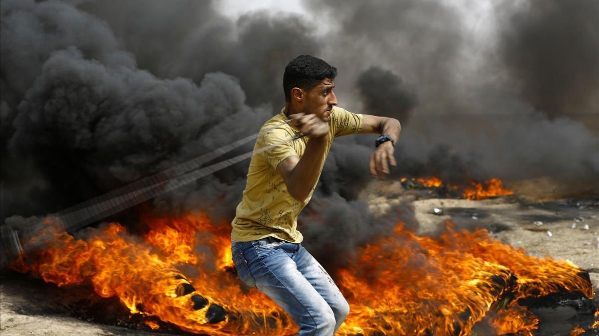 Un palestino se dispone a lanzar piedras entre los neumáticos incendiados contra las tropas israelís, en las protestas junto a la frontera de la Franja de Gaza, el 20 de abril.