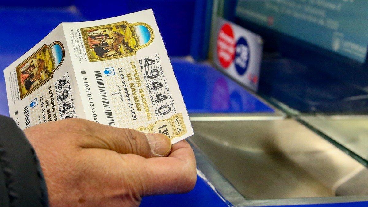 Persona comprando un décimo de la Lotería de Navidad 2020.