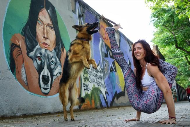Kaitlyn Patrizia, con su perro, 'Naitra', haciendo yoga ante uno de los grafitis del Poblenou.