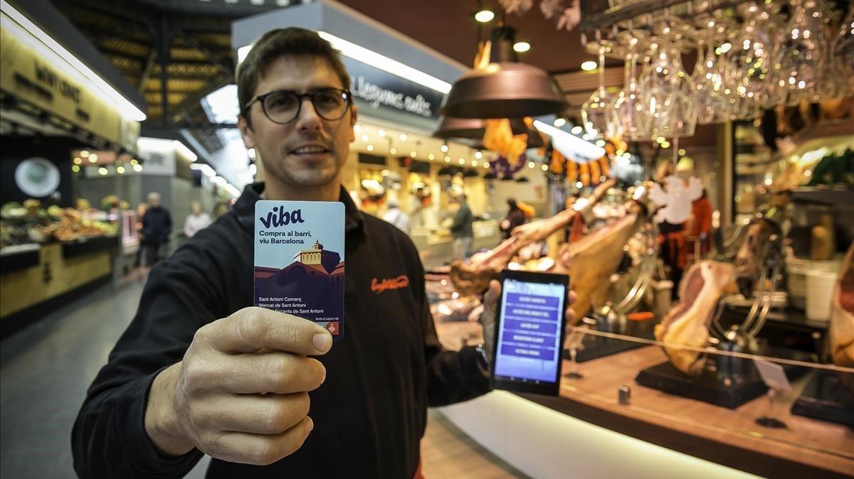El comerciante Jaume Escofet cobrando a un cliente con la nueva tarjeta,en su parada del merdado de Sant Antoni.