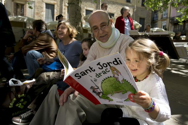 Una niña lee un libro sobre la leyenda de Sant Jordi en compañía de su abuelo.