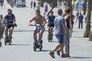 Tres usuarios de patinete eléctrico, en el paseo marítimo de la Barceloneta.