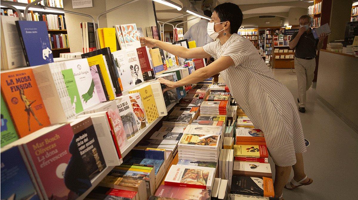 Una empleada recoloca varios libros en las estanterías de la librería Laie de Barcelona, el pasado 21 de julio.