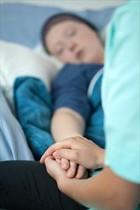 Una enfermera sostiene la mano de una enferma que recibe curas paliativas.
