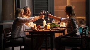 Una familia brinda mientras cena.